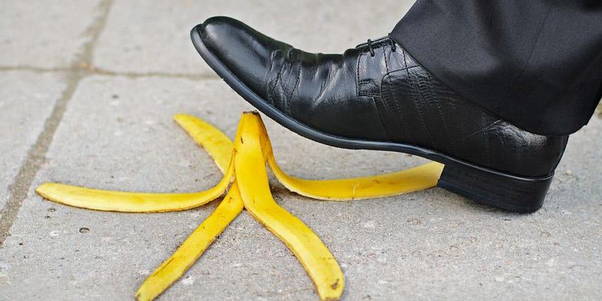 Mann steigt auf Bananenschale