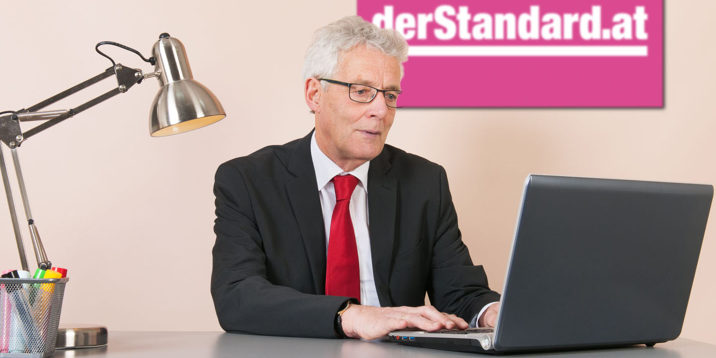 Alter Mann mit Laptop vor DerStandard.at-Schild