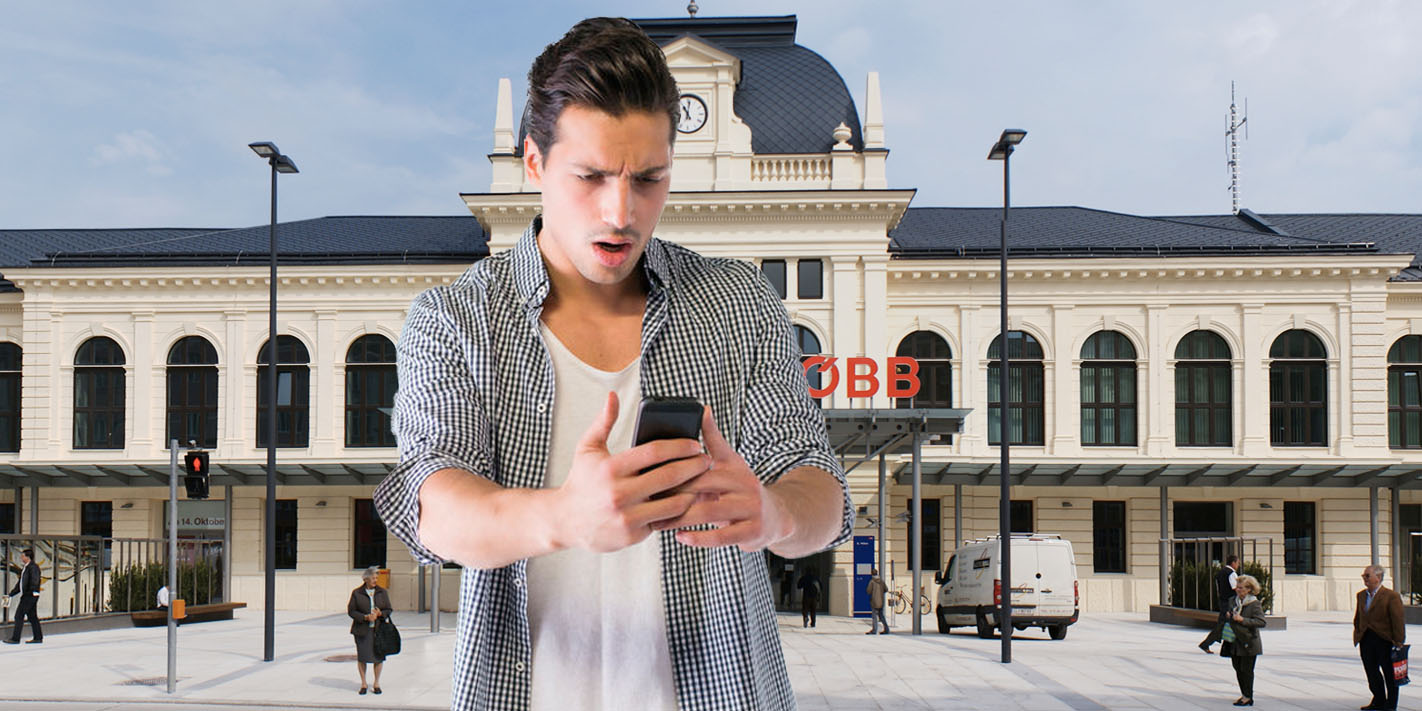 Mann mit Handy vor dem Bahnhof von St. Pölten