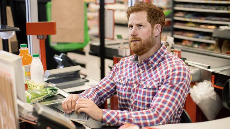 Prinz Harry sitzt an einer Supermarkt-Kassa und schaut demotiviert