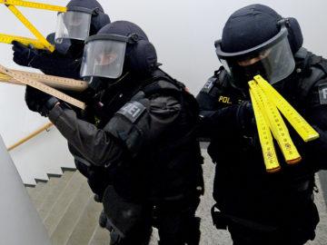 Polizisten mit Zollstöcken