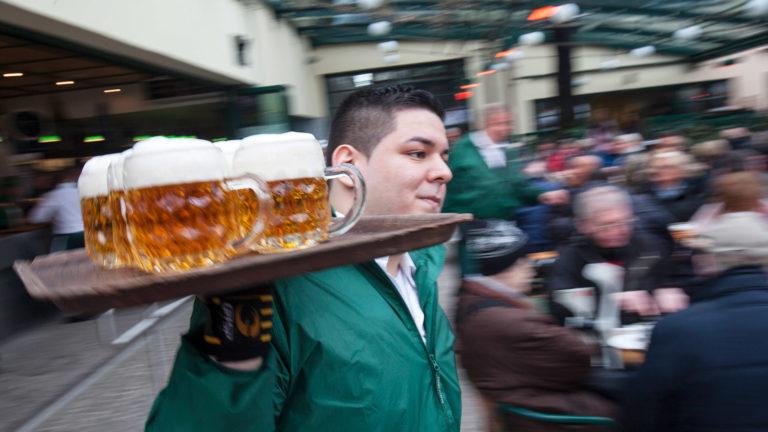 Kellner trägt Bier