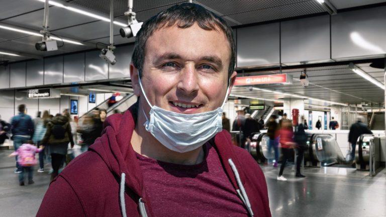 Mann mit Maske auf Kinn in U-Bahn-Station