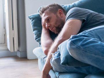 Mann liegt deprimiert auf der Couch
