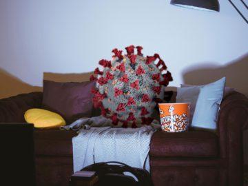 Corona sitzt auf Couch vor Fernseher