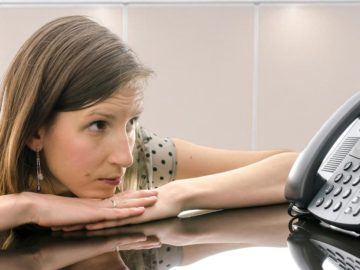 Frau starrt Telefon an