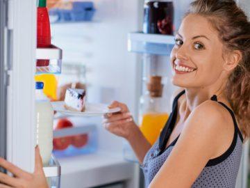 Glückliche Frau nimmt Kuchenstück aus Kühlschrank