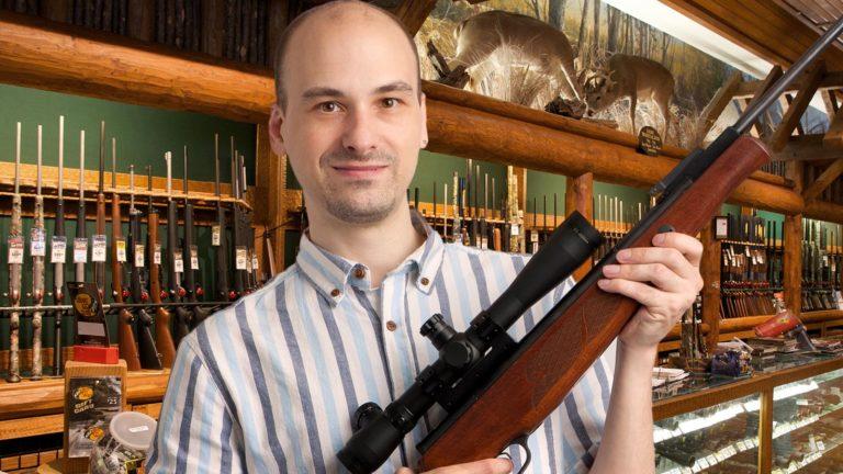 Mann mit Gewehr im Waffengeschäft