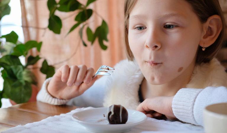 Mädchen isst begeistert Rumkugeln