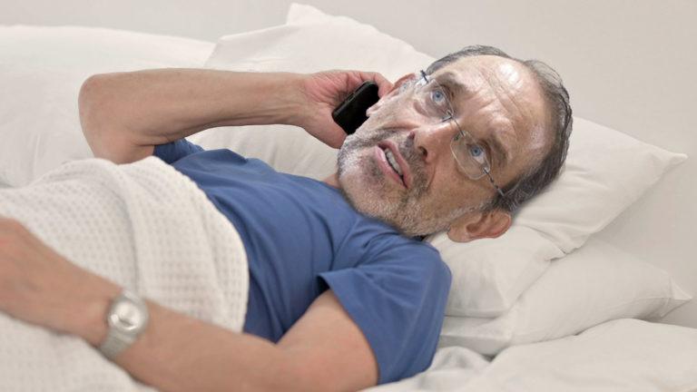 Faßmann telefonierend im Bett