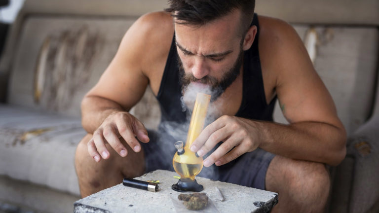 Mann raucht Bong