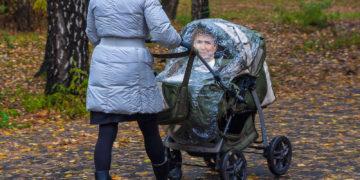 Frau schiebt Kinderwagen, darin sitzt Kurz