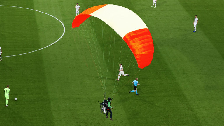 Rot-weiß-roter Gleitschirm über Fußballfeld