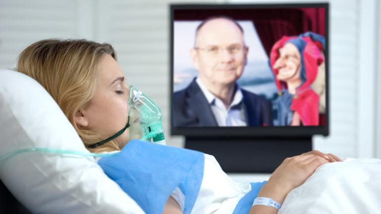 Patientin im Bett, am Herzmonitor läuft Servus TV