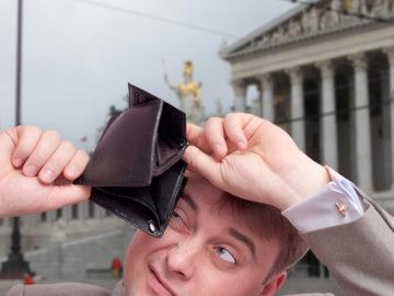 Geschäftsmann betrachtet seine leere Geldbörse vor dem Parlament