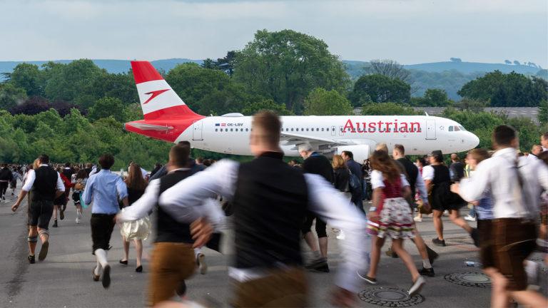 Menschen in Lederhose laufen zu einem Flugzeug